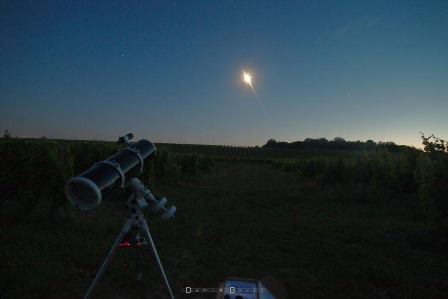 Paysage valloné avec des vignes au crépuscule, la Lune (surexposée) est visible juste au dessus du l'horizon. Télescope de couleur noir sur une monture équatoriale, à gauche.