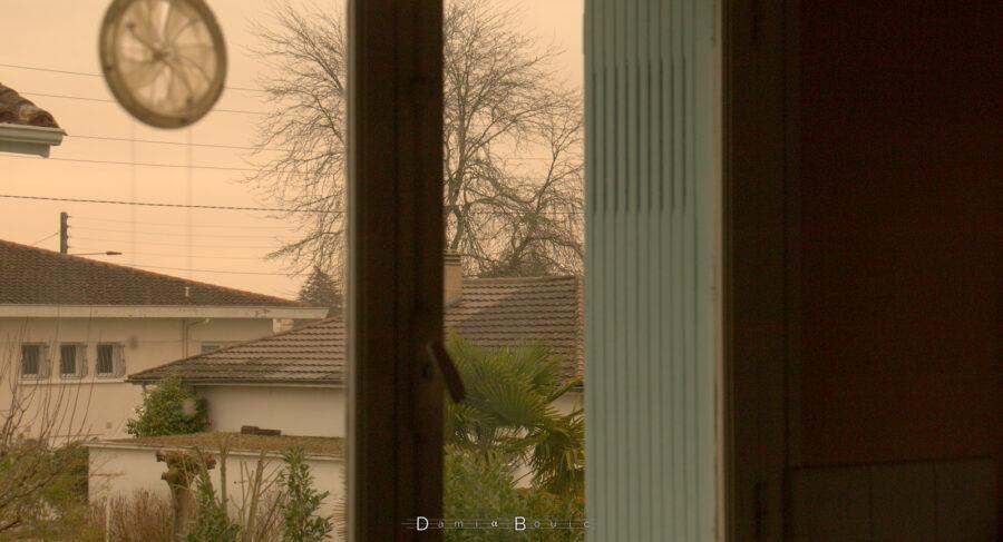 Vue resserrée au travers d'une fenêtre, montrant quelques maisons pavillonnaires, un arbre décharné et un ciel ocre
