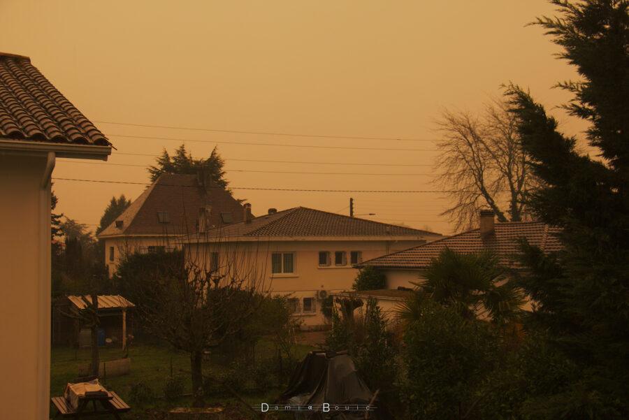 Photo montrant quelques maisons sous un ciel franchement orange