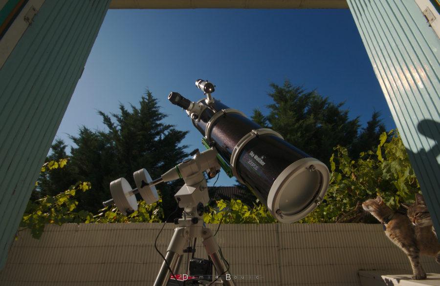 Télescope noir sur une monture blanche, dirigé vers le ciel bleu
