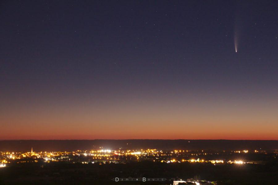 Vallée plongée dans le noir, ville lumineuse, dégradé coloré évoquant l'aube, comète à droite dans le coin