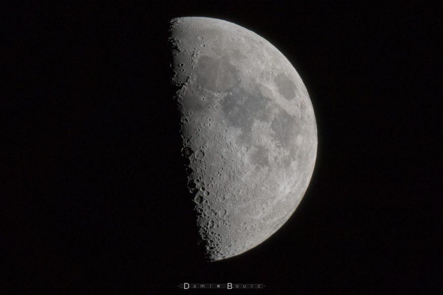 Quartier de Lune regardant vers la droite, de nombreux cratères sont visibles sur la ligne du terminateur