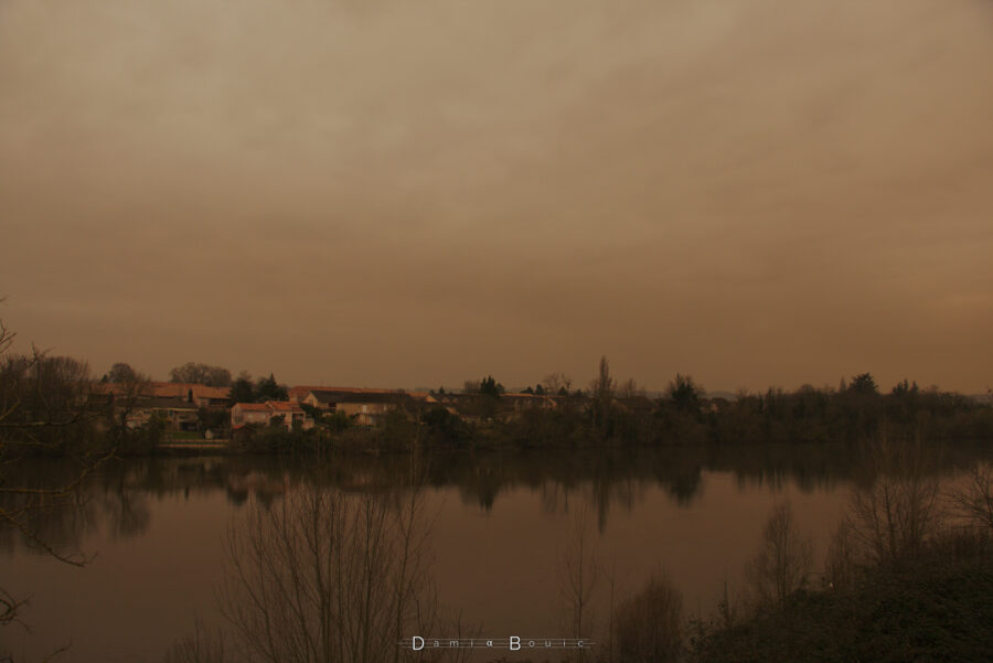 Vue sur le Sud, en plan large, avec la Dordogne et la vue sur la rive opposée, sous un ciel nuageux sombre et ocre