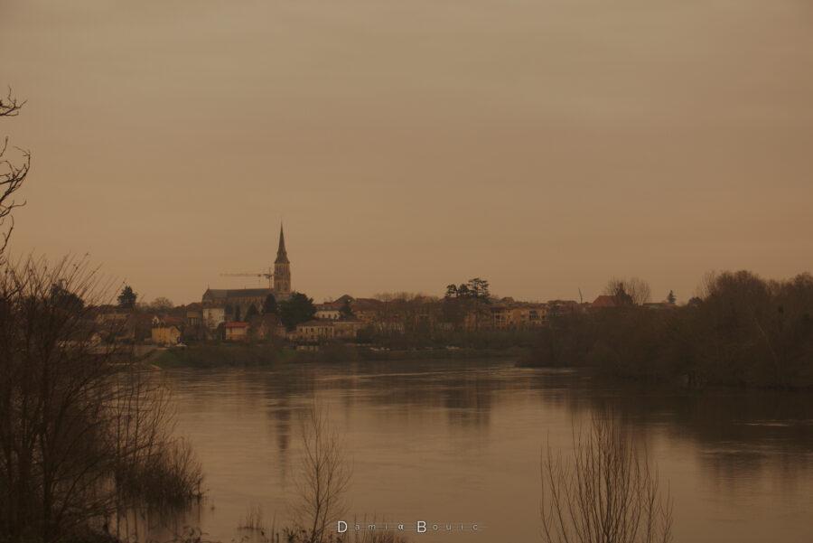 Vue centrée sur Bergerac, au loin, sur la Dordogne, toujours sous ce ciel jaune