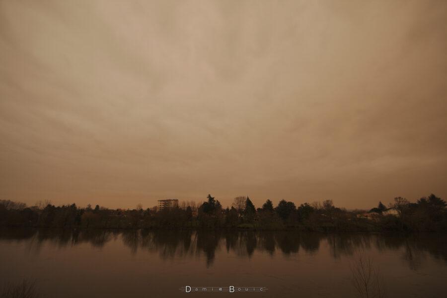 Photo en ultra-grand angle montrant le ciel jaune-orange, irrégulier, et du paysage en dessous (ligne d'horizons constituée majoritairement d'arbres, d'un seul immeuble de 6 étages, le tout se reflétant dans l'eau de la Dordogne)