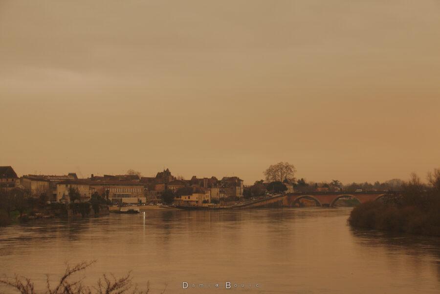 Zoom sur le Vieux Bergerac, avec le pont en pierre dont la partie centrale est masquée par l'île, le tout dans cette ambiance jaune
