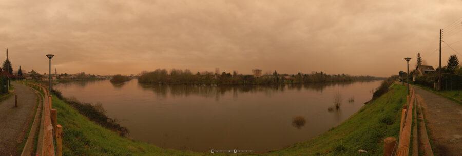 Image panoramique, donc déformée, montrant tout le fleuve Dordogne, qui adopte une allure de large sourire, avec un ciel aux couleurs chaudes