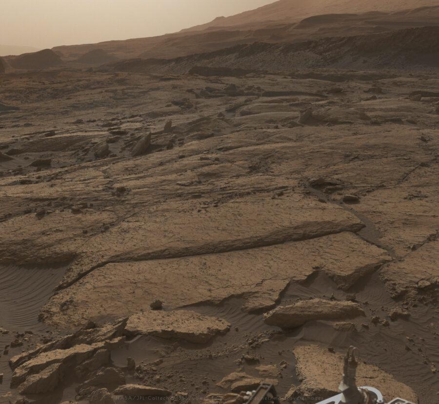 Paysage martien en fin d'après-midi, en contrejour. L'éclairage est rasant, les teintes rouilles du paysages sont amplifiées, l'ambiance paraît poussiéreuse.