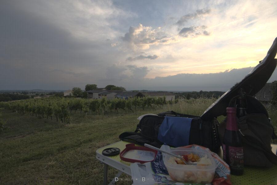 Premier plan, table de camping à droite avec un sac photo ouvert, un plexi ouvert avec une salade de tomates-mozza et une fourchette plongée dedans. Une bière aromatisée à la framboise est visible à droite. Couvercle et bouchon d'objectif trainent sur le coin gauche de la table. Paysage : herbe rase, vignes qui descendent, bâtiment viticole derrière. Horizon dégagé et ciel encombré, sombre à gauche plus clair à droite avec de nombreux morceau de nuages écorchés.