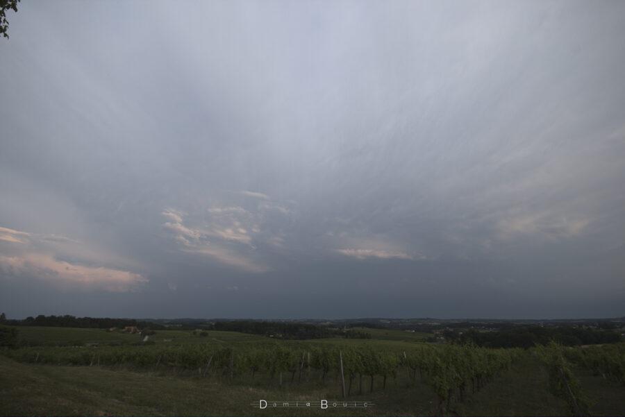 Paysage de vignes et de collines dégagé. Ciel sombre au loin, des nuages plus clairs à la faveur du Soleil couchant.