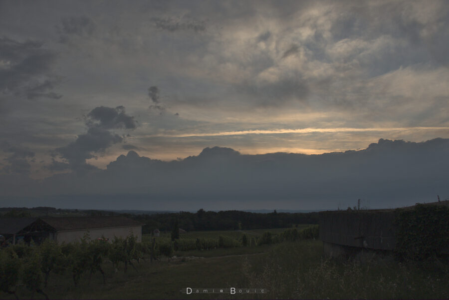 Le Soleil se couche mais il n'est pas visible, masqué par une barre de nuages sombre et compacte. Ces nuages sont boursoufflés par ailleurs. Le reste du ciel est teinté de lumière solaire et de rugosités nuageuses.