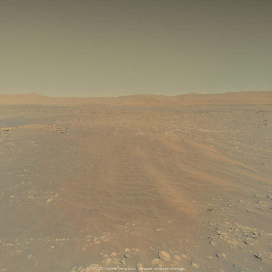A picture from Ingenuity drone, showing the martian landscape from a few meters above the ground. We can see dunes, some boulders, and on the horizon, some hills