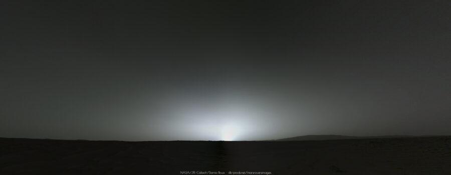 Coucher de soleil martien dans des teintes métalliques, l'horizon se découpe nettement, droit comme l'horizon maritime. Seul à droite on trouve une colline allongée