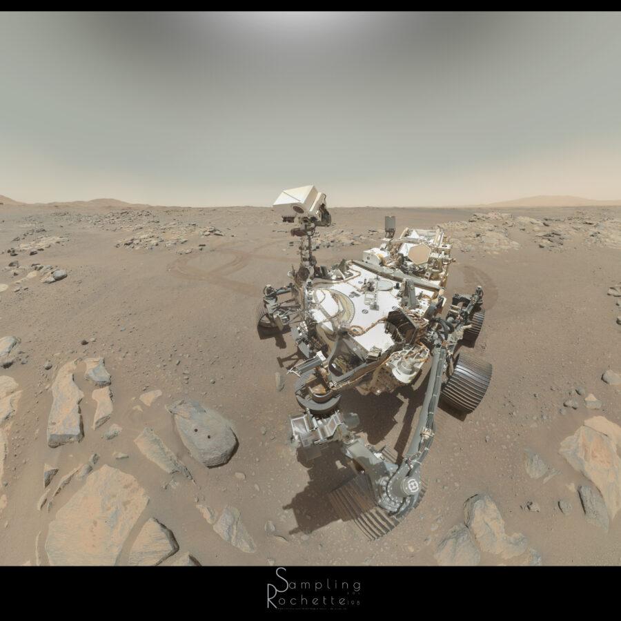 Le rover Perseverance, vu de 3/4, regardant un rocher gris percé de deux trous. D'autres roches entourent le rover, à sa gauche derrière lui les traces de roues témoignent de plusieurs manœuvres. Au loin, horizon légèrement ondulé, et ciel dégagé.