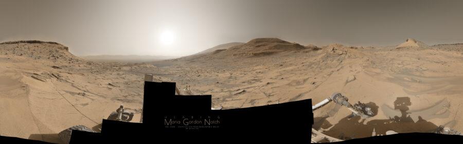 Panorama couleur de Mars. Le Soleil est bas sur l'horizon, les ombres sont étirées en direction du Soleil. De nombreuses collines sont visibles depuis le centre vers la droite, mais son moins nombreuses à mesure que l'on va vers la bordure droite. Un pic rocheux plus clair est sur l'horizon juste avant le bord de l'image. Au centre gauche, l'horizon va loin, on distingue une barrière montagneuse dans le lointain et la brume atmosphérique. Puis, en allant vers la gauche, le regard butte sur une falaise rocheuse au sommet arrondi. Le sol est globalement lisse, avec de nombreuses craquelures. Le rover n'est présent que par morceaux, le reste de son corps n'étant pas intégré à la mosaique. On peut voir le bras robot déployé et posé sur le sol rocheux lisse à droite en bas, et un peu plus à droite, l'ombre du mât des caméras